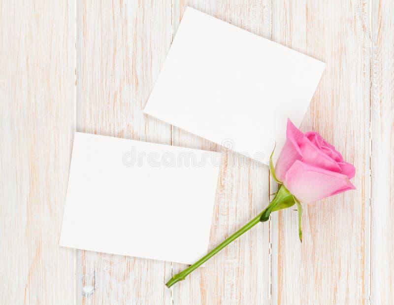 Leere Fotorahmen und Rosarose über Holztisch stockfotos