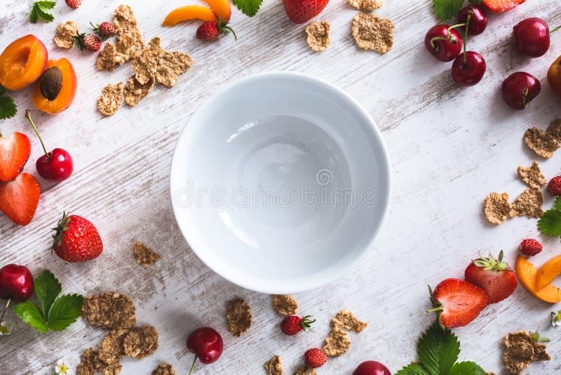 Leere Frühstücks-Schüssel mit Getreide, Kirschen, Aprikose, Erdbeeren lizenzfreies stockfoto