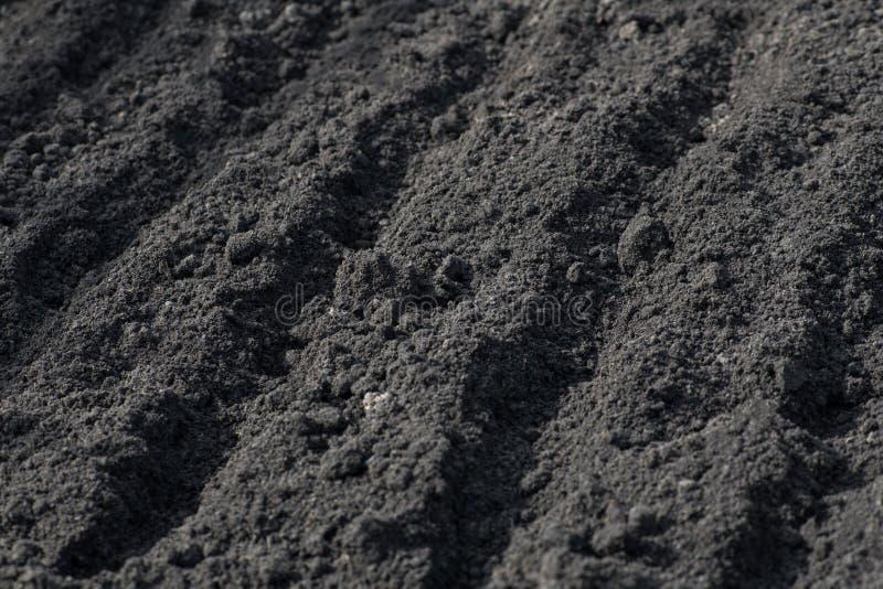 Leere Furchen auf schwarzem Boden auf einem Bauernhofgebiet im Vorfrühling Vorbereitung des Bodens für das Pflanzen von Samen Gel stockfotos