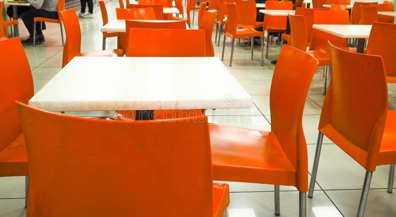 Leere gelbe Farbstühle vereinbart in der Reihe mit dem unscharfen Leutehintergrund in der Halle Esszimmer mit orange Stühlen, stockfoto