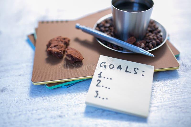Leere gewundene Notizblöcke, Tasse Kaffee und Stift auf hölzernem Hintergrund lizenzfreie stockfotos