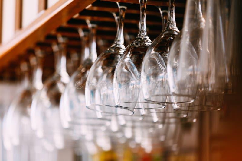 Leere Gläser für Wein über einer Bar beanspruchen stark Hängende Weingläser herein stockbild