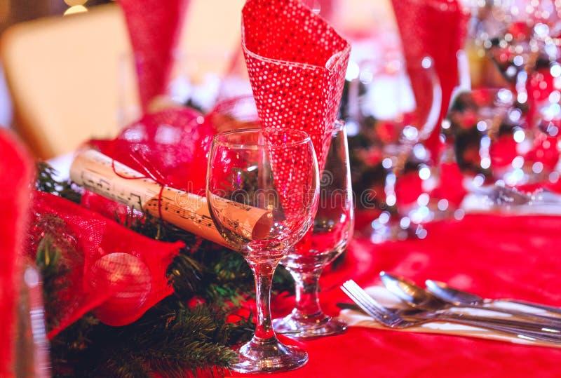 Leere Gläser stellten in Esszimmer mit roter Feiertagsdekoration ein stockfotos