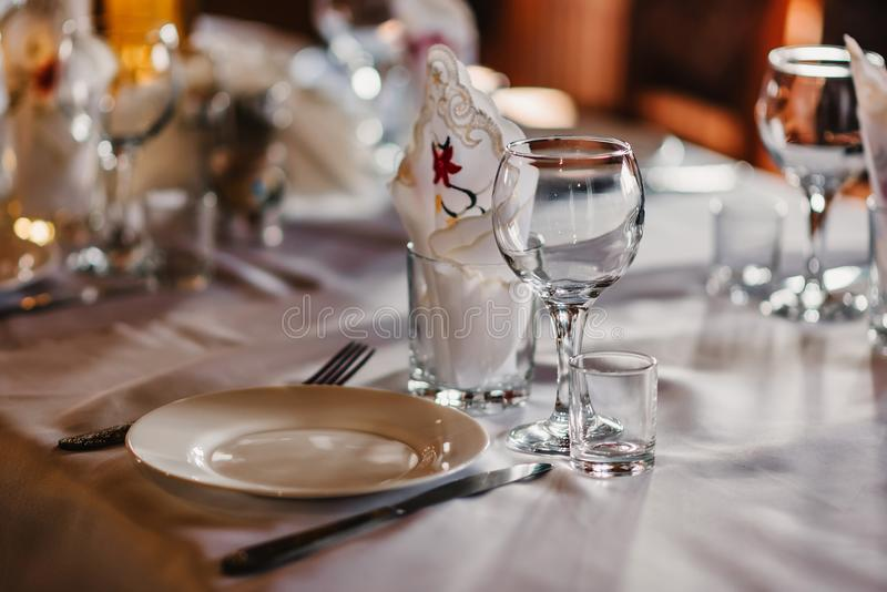 Leere Gläser und Teller mit Cutlery auf einem weißen Tischdecken auf dem Tisch im Restaurant lizenzfreie stockbilder