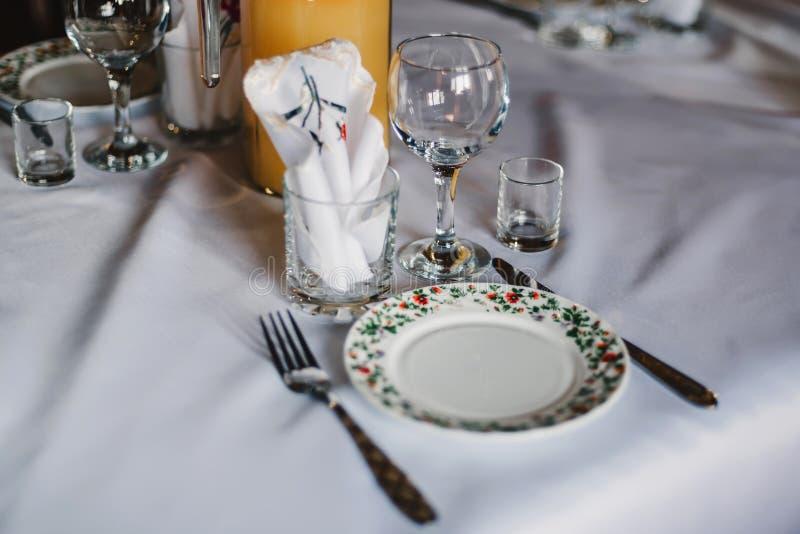 Leere Gläser und Teller mit Cutlery auf einem weißen Tischdecken auf dem Tisch im Restaurant lizenzfreie stockfotografie