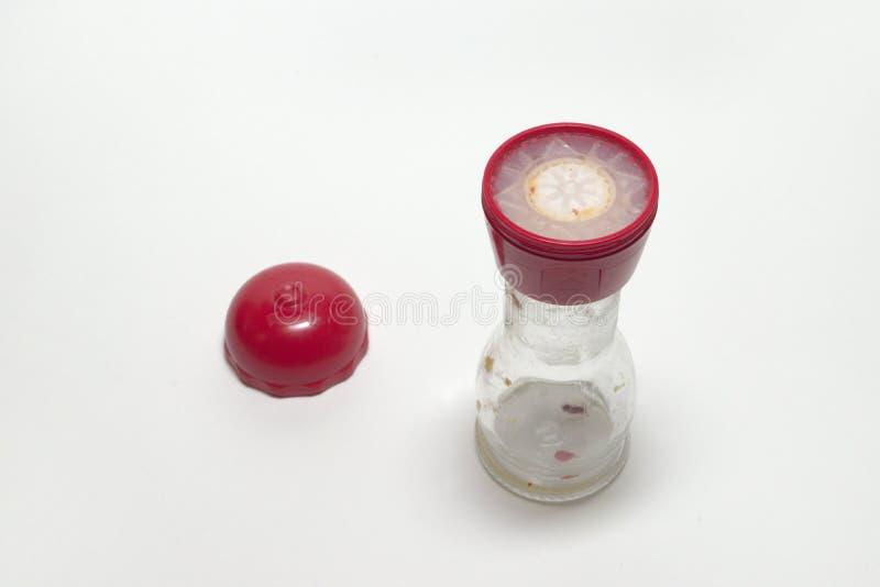 Leere Glaspfeffermühle mit zwei Graden Schleifen, mit dem Rot stockfotografie