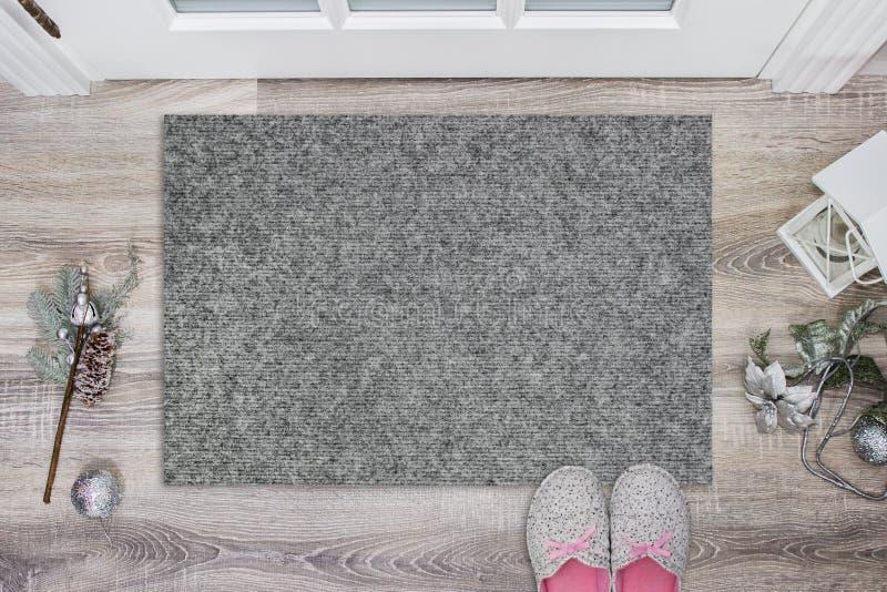 Leere graue Fußmatte vor der Tür in der Halle Matte auf Bretterboden, mit Weihnachtsdekoration und Pantoffeln willkommen lizenzfreie abbildung