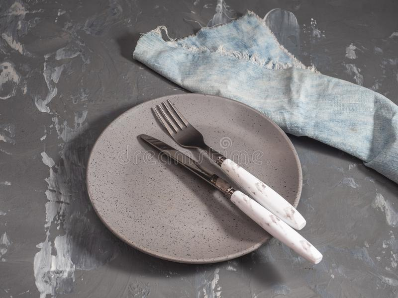 Leere graue keramische Platte auf einem grauen beschmutzten Hintergrund und Tischbesteck mit den Griffen, zum der Hintergrundfarb lizenzfreies stockfoto
