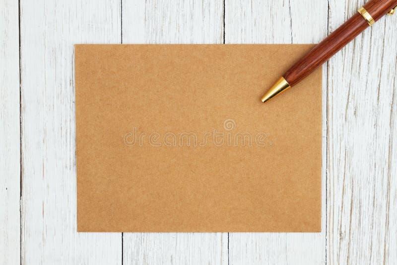 Leere Grußkarte Browns mit Stift auf verwittertem strukturiertem Holzhintergrund der Tünche stockfotografie