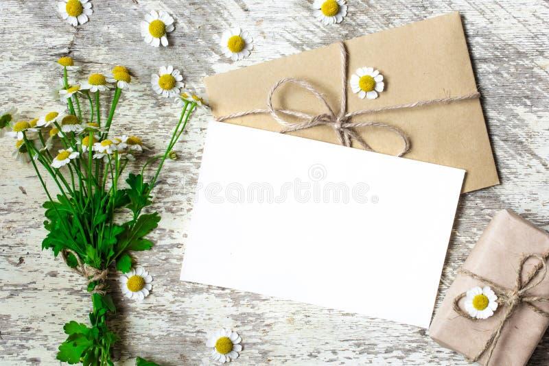 Leere Grußkarte und -umschlag mit weißen Kamillenblumen und Weinlesegeschenkbox stockbilder