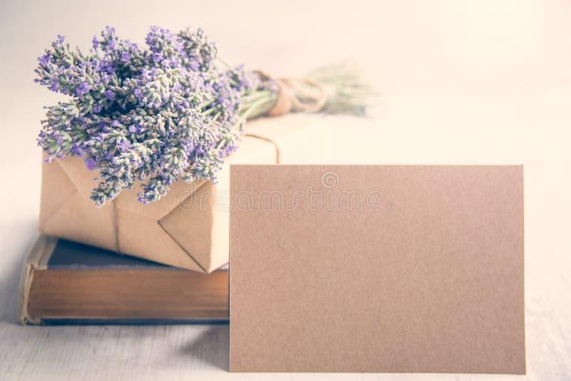 Leere Grußkraftpapier-Karte vor einem Lavendelblumenstrauß, einem eingewickelten Geschenk und einem alten Buch über einem weißen  stockfoto