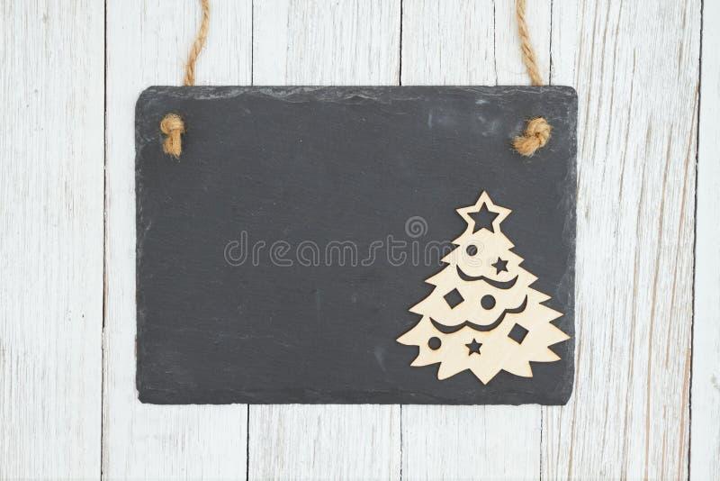 Leere hängende Tafel mit einem Weihnachtsbaum auf verwittertem strukturiertem Holzhintergrund der Tünche lizenzfreie stockfotos