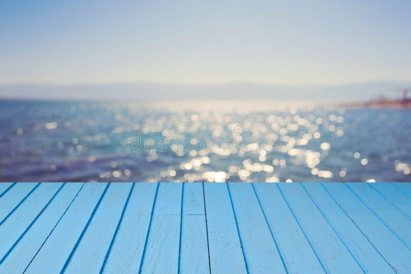 Leere hölzerne blaue Tabelle über Meer-bokeh Hintergrund Tropisches Plakat lizenzfreies stockbild