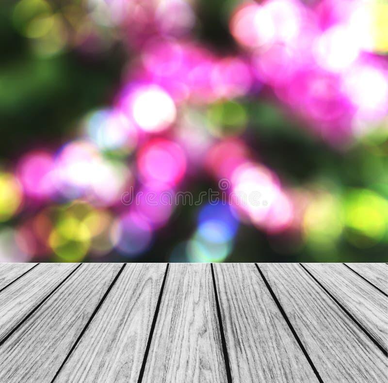 Leere hölzerne Perspektiven-Plattform mit funkelnder abstrakter Regenbogen-Unschärfe Bokeh verwendet als Schablone, um für Anzeig stockfoto