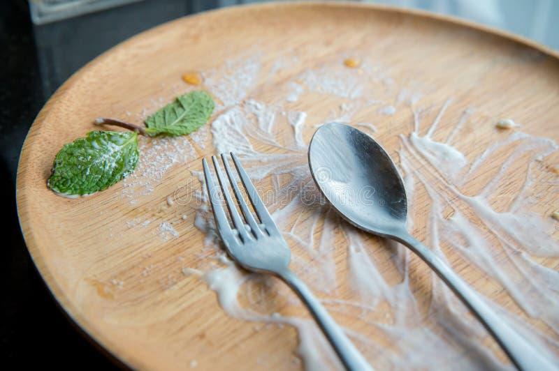 leere hölzerne Platte mit, Löffel, Gabel und tadelloser Urlaub Nachdem Nachtisch gegessen worden ist stockbild