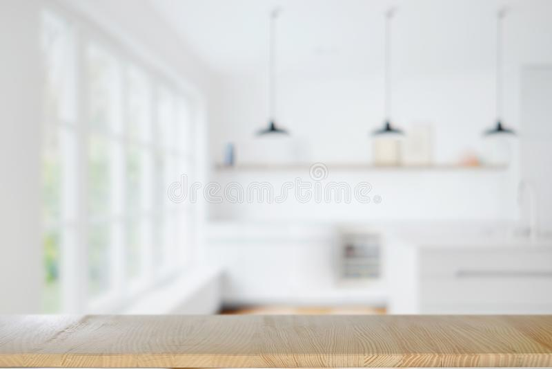 Leere hölzerne Tabelle über modernem hellem Innenraum von Küche backgroun stockfotografie