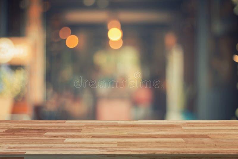 Leere hölzerne Tabelle und unscharfe Hintergrundanzeige an der Kaffeestube stockfoto