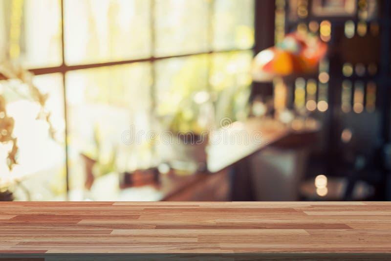 Leere hölzerne Tabelle und unscharfe Hintergrundanzeige an der Kaffeestube stockbild