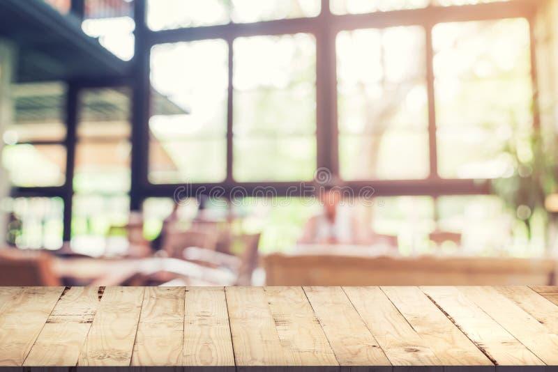 Leere hölzerne Tabelle und unscharfer Hintergrund: Kunde an Kaffee sho lizenzfreies stockbild