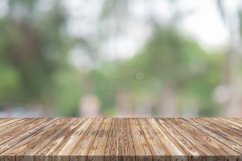Leere hölzerne Tischplatte auf grünem Unschärfehintergrund am Garten lizenzfreies stockfoto