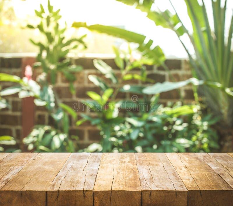 Leere hölzerne Tischplatte auf Unschärfezusammenfassungsgarten- und -haushintergrund stockfoto