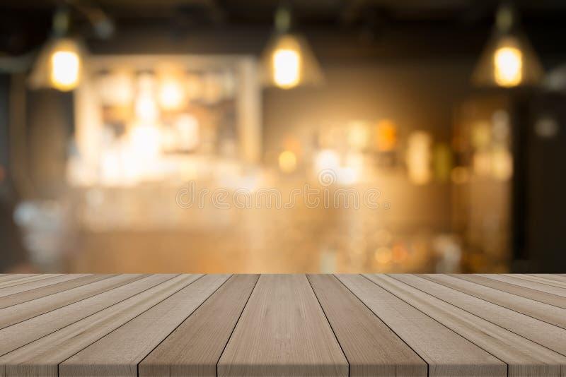 Leere hölzerne Tischplatte auf unscharfer Hintergrundformkaffeestube stockbilder