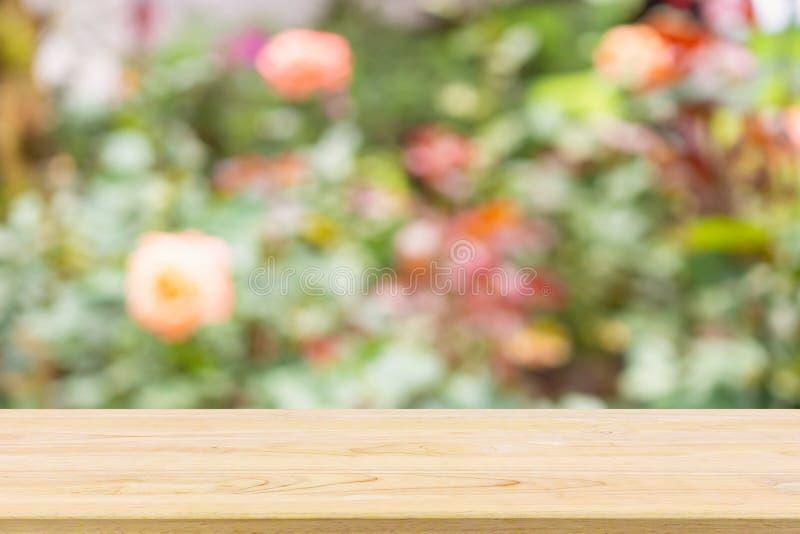 Leere hölzerne Tischplatte mit bunten rosafarbenen Blumen der Zusammenfassungsunschärfe im Garten natürlichen bokeh Lichthintergr lizenzfreie stockfotos