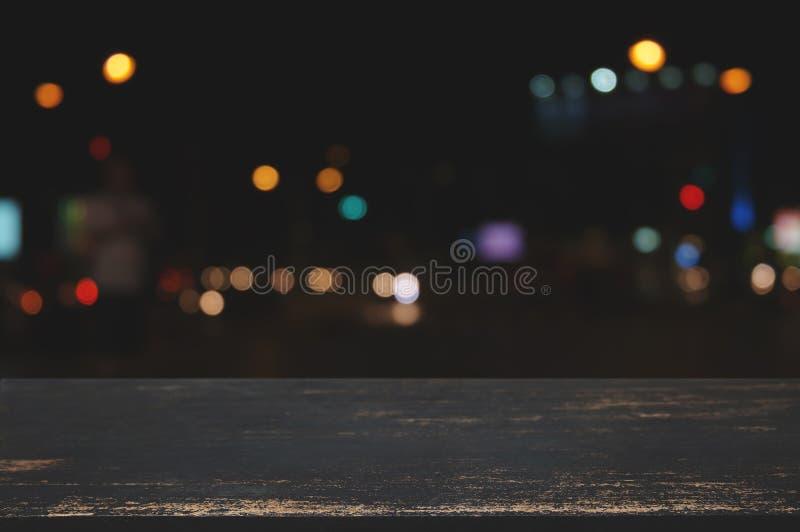 Leere hölzerne Tischplatte mit Unschärfenachtmarkt-Lichthintergrund stockbilder