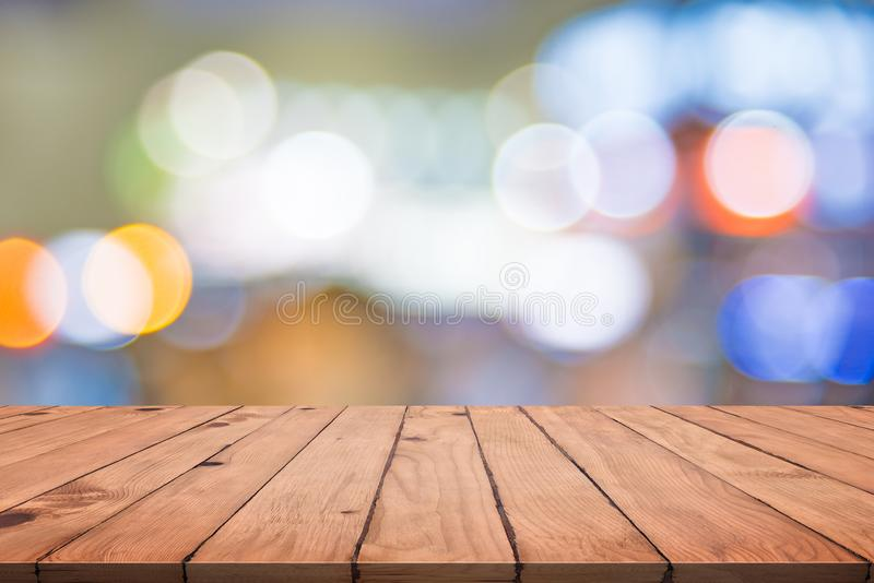 Leere h?lzerne Tabelle mit buntem abstraktem bokeh Tapete und Beschaffenheitskonzept Stadtlicht und Produktstadiumsvertretungsthe stockfotografie
