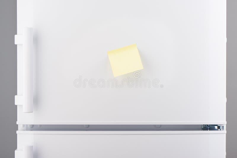 Leere hellgelbe klebrige Papieranmerkung über weißen Kühlschrank stockfotografie