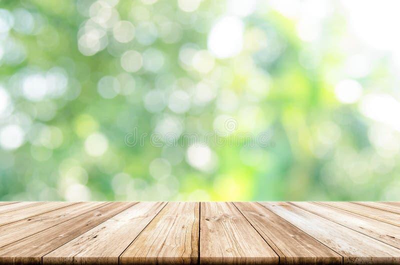 Leere Holztischspitze mit unscharfem grünem Gartenhintergrund stockfoto