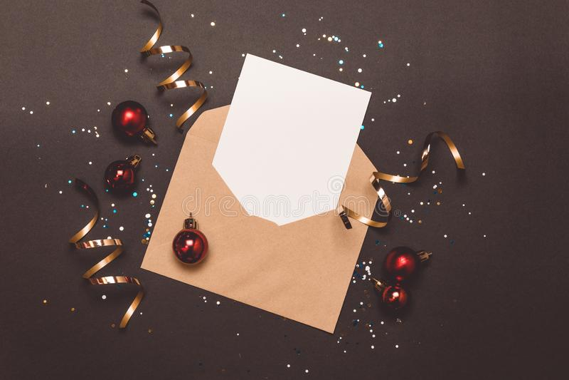 Leere Karte des Weihnachtszusammensetzungsfeiertags-Modells im Umschlag auf schwarzem Hintergrund Flache Lage, Draufsicht lizenzfreies stockfoto