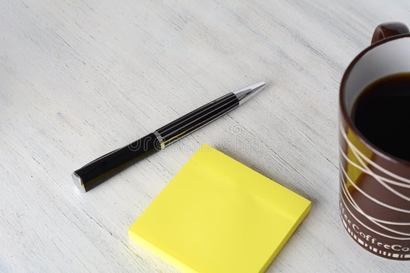 Leere klebrige Anmerkung mit Tasse Kaffee und Stift lizenzfreie stockbilder