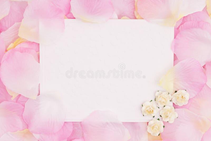 Leere Liebesgrußkarte auf rosa rosafarbenen Blumenblumenblättern lizenzfreie stockbilder