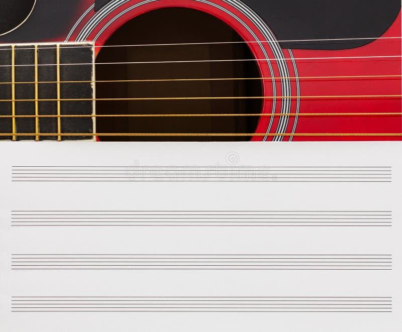 Leere Musiknotizbuchseite mit Kopieraum, auf roter Gitarre mit sechs Streicher Musikunterrichtkonzept lizenzfreie stockfotografie