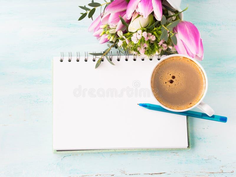 Leere Notizbuchseite mit blauem Stift- und Schalenkaffee blüht lizenzfreie stockbilder
