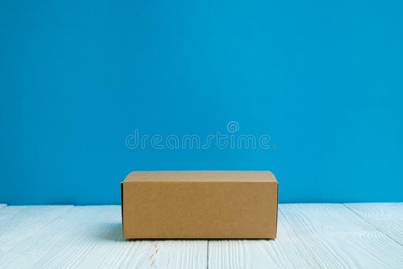 Leere Paketbraunpappschachtel oder -behälter auf hellem weißem hölzernem lizenzfreie stockfotografie