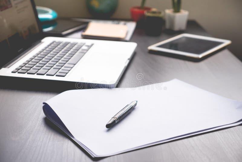 Leere Papiere mit Stift, Tablette und Laptop auf dem Schreibtisch stockfotos