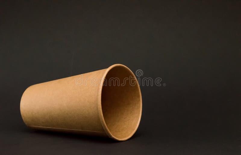 Leere Papierschale f?r Kaffeel?gen auf seiner Seite auf einem schwarzen Hintergrund, fiel Glas lizenzfreie stockfotos