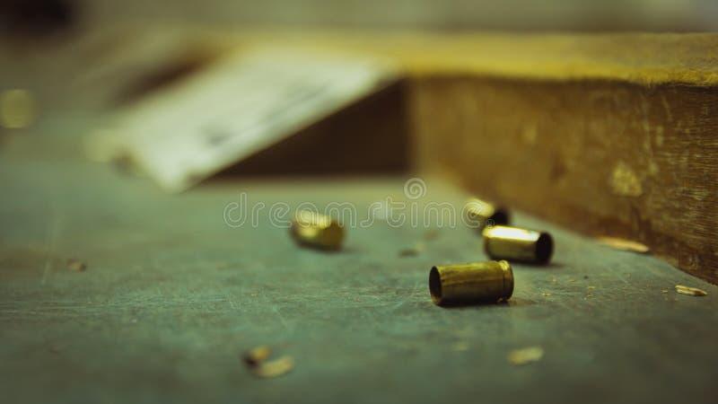 Leere Pistolenkugeloberteile auf Holztisch in einem Schießstand stockbild