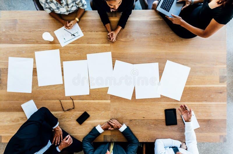 Leere Plakate auf Tabelle mit den Geschäftsleuten, die herum sitzen stockfoto