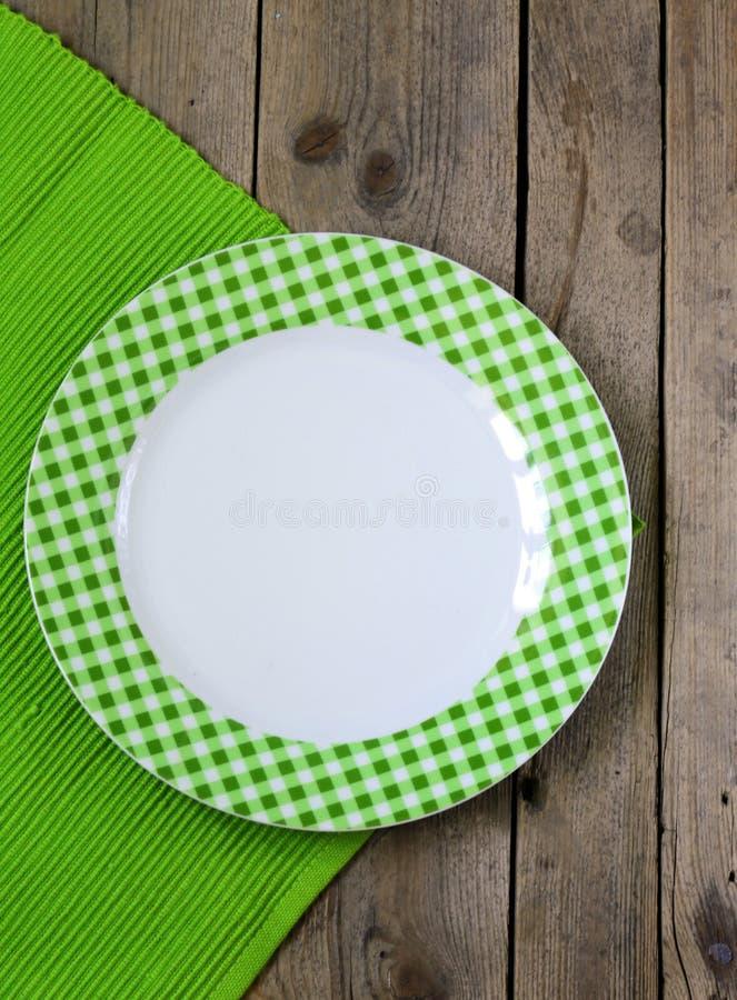 Leere Platte auf einem hölzernen Hintergrund mit Serviette lizenzfreie stockfotografie