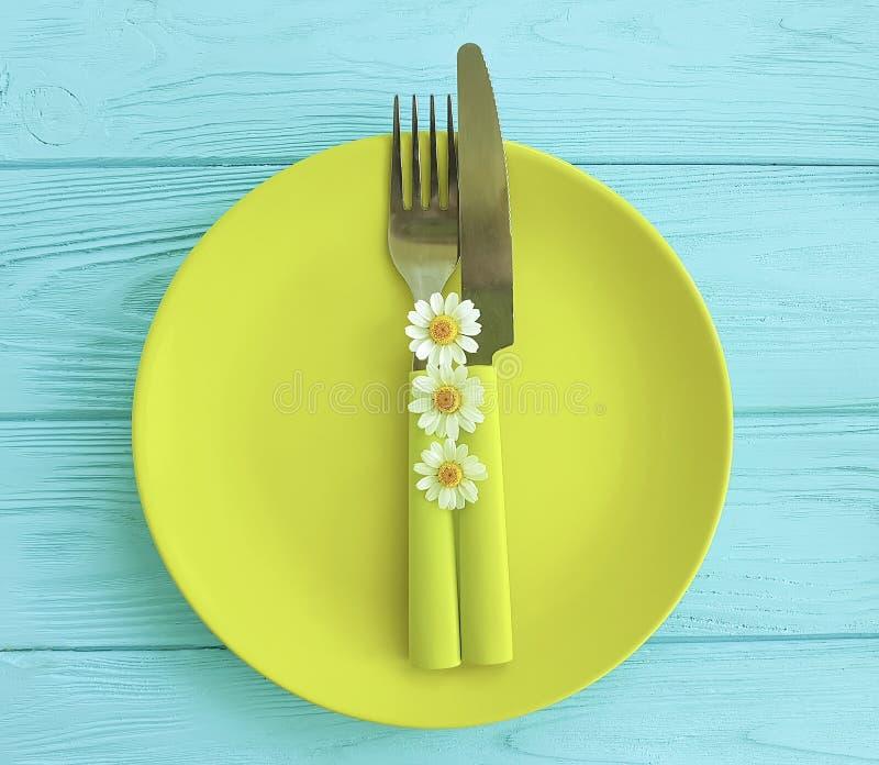leere Platte auf einer blauen hölzernen Hintergrundgänseblümchen-Blumengabel, Messer lizenzfreie stockfotos