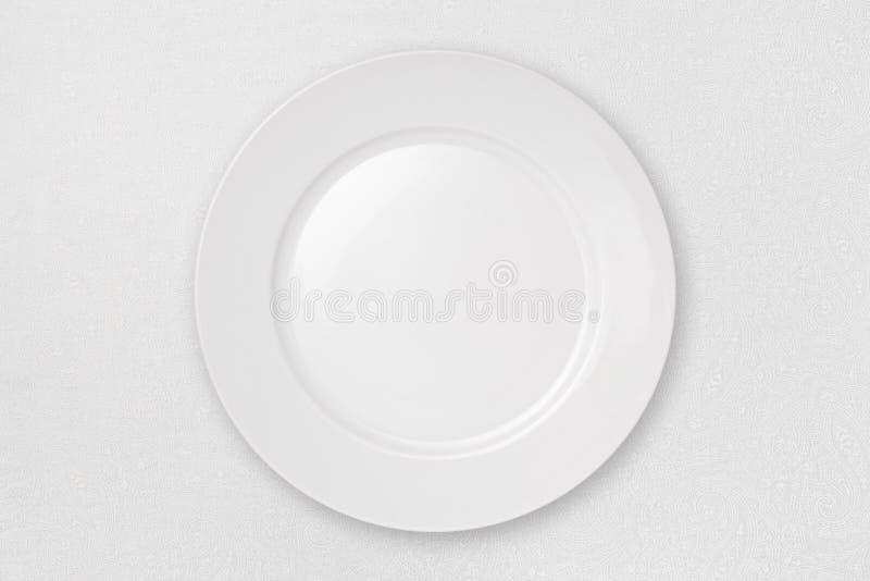 Leere Platte auf einer weißen Tischdecke lizenzfreie stockbilder