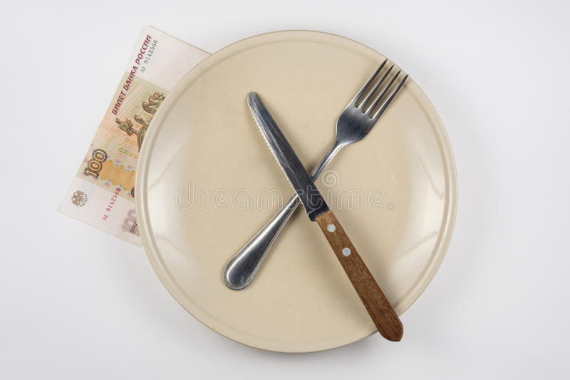 Leere Platte mit Gabel und Messer, Abschluss ist HundertRubel-Anmerkung, weißer Hintergrund stockfotos