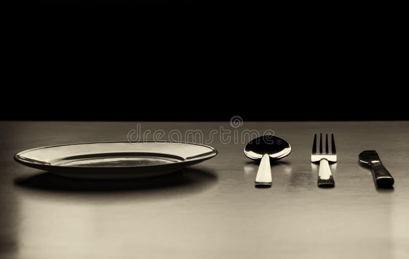 Leere Platte mit Löffel, Messer und Gabel auf einem schwarzen Hintergrund stockfoto