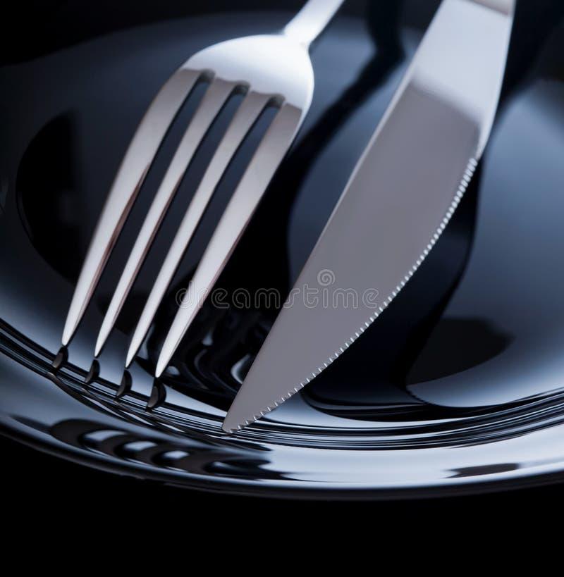Leere Platte mit Messer und Gabel auf einem schwarzen Hintergrund lizenzfreie stockfotos