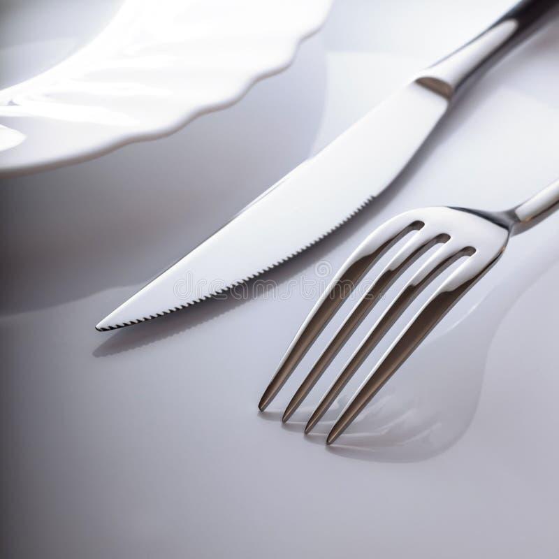 Leere Platte mit Messer und Gabel auf einem weißen Hintergrund lizenzfreie stockfotos