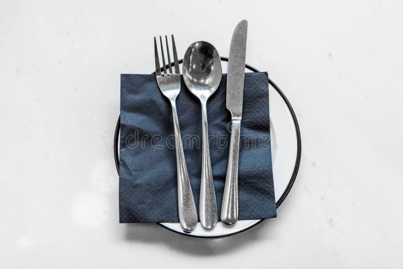 leere Platte mit Messerlöffel und Gabel auf Tabelle stockfotografie