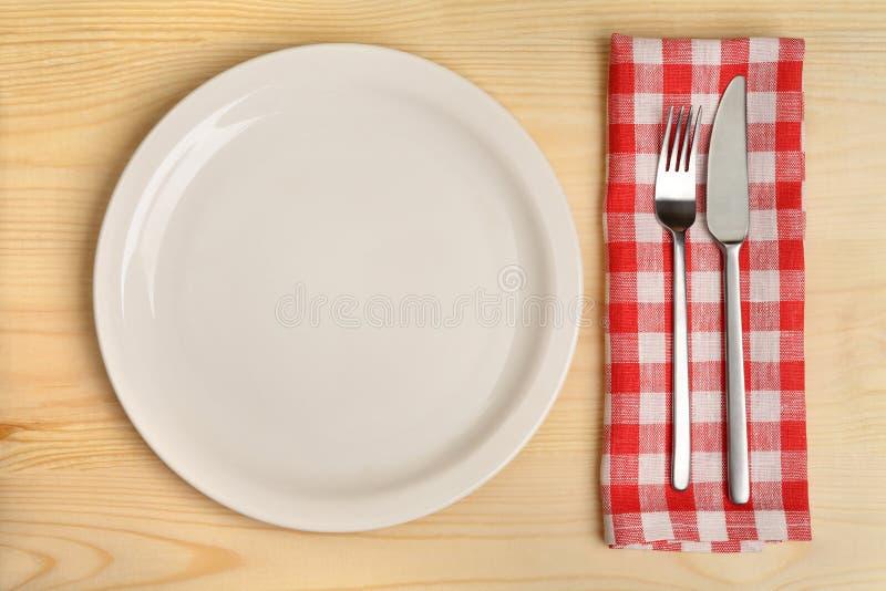 Leere Platte mit Tischbesteck auf roter karierter Serviette auf hölzernem Hintergrund lizenzfreies stockfoto
